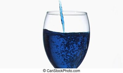 Thin blue trickle in super slow motion flowing in a full wine glass