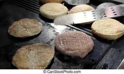 Thin burger meat on pan. Sliced round buns. Chicken patties...