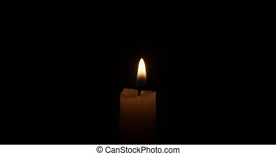 thin candle burning over dark background, 4k prores footage