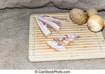 Thin cut bacon on a wooden board