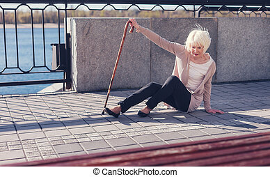 Thin elderly woman trying to get up from the pavement
