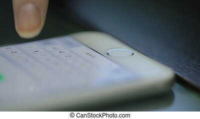 Thin female fingers glide across the screen of her smartphone virtual keyboard on the gray table