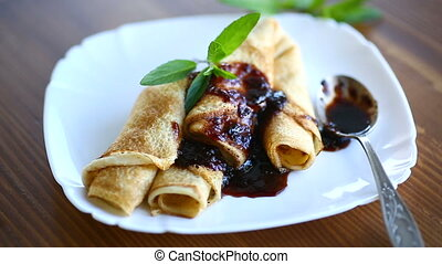 thin fried pancakes stuffed with jam in a plate on a wooden...