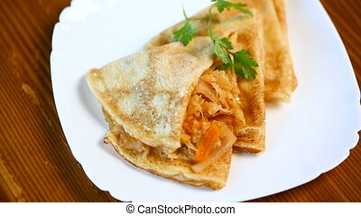 thin fried pancakes stuffed with stewed cabbage in a plate...