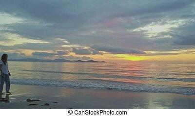 Thin Girl Walks on Wet Sand Beach against Sea Sunrise