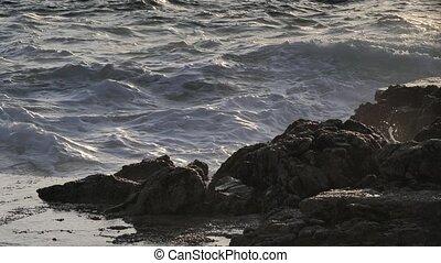 Thin hard rocky land in foamy sea.