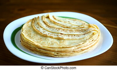Thin pancakes stacked on a plate in a pile - Thin pancakes...