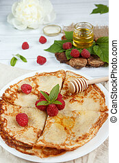 Thin pancakes with honey and raspberries on a white plate