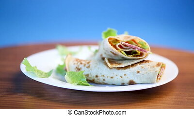thin pancakes with salad leaves and bacon in a plate on a...