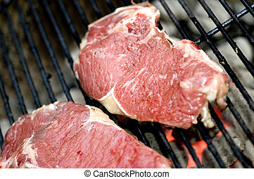 thin sliced shell steaks on grill - thin sliced beef loin...
