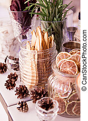 Thin slices of dried pear orange lemon beet. On the table, glass jars with dried fruits beside lie cones