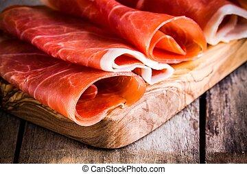 thin slices of prosciutto closeup on a cutting board