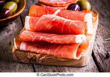 thin slices of prosciutto with olives on a cutting board