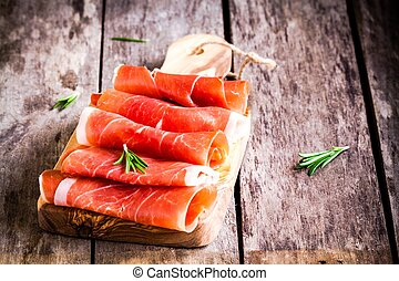 thin slices of prosciutto with rosemary on a cutting board
