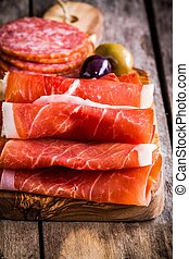 thin slices of prosciutto with salami on a cutting board