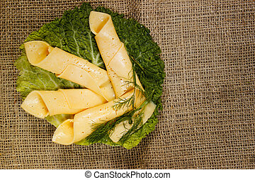thin slices of yellow cheese rolled into a straw on a green salad sheet on burlap.