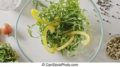 Thin strips of chopped yellow pepper paprika fall into a glass bowl with green arugula. Background with tomatoes, pumpkin seeds, salt and pepper. Top view. Full HD video, 240fps,1080p