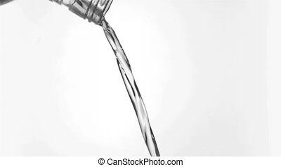 Thin tickle of water in a super slow motion flowing from the glass bottleneck