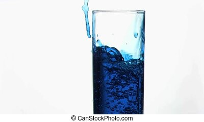 Thin trickle blue in super slow motion overflowing in a glass