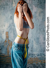 Thin woman in jeans measures waist, weight loss
