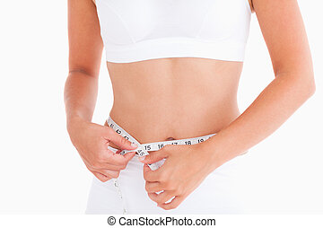 Thin woman measuring her waist