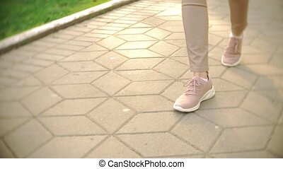 thin women's legs in beige trousers and sneakers stroll in...