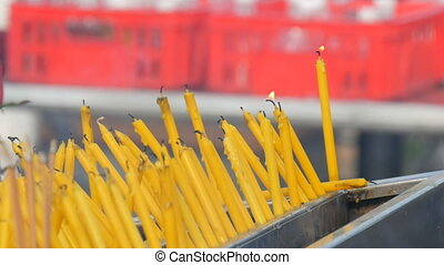 Thin yellow wax candles glow before altar - Thin yellow wax...