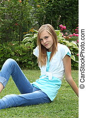 Thin young teenage girl relaxing on the lawn