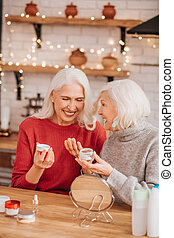 Two good-looking elderly women enjoying skin treatment