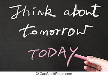 Think about tomorrow today words written on the blackboard ...