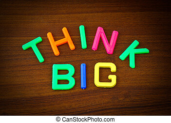 Think big in colorful toy letters on wood background