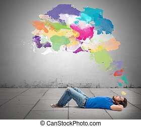Think creative - Lying boy think creative with colorful...
