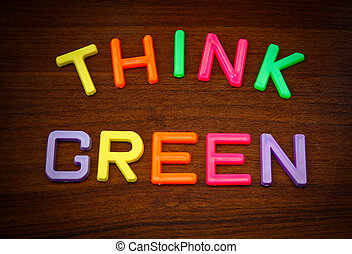 Think green in colorful toy letters on wood background