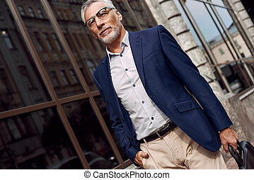 Think through a business meeting. Elegant man in casual suit smiling while walking outdoors