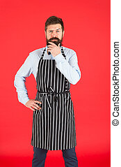 Thinking about new recipe. Elegant waiter man or bartender. Bearded man wearing bib apron. Man cook with beard and mustache in cooking apron. A thoughtful man servant