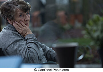 Thinking about old times - Aged sorrowful woman thinking...