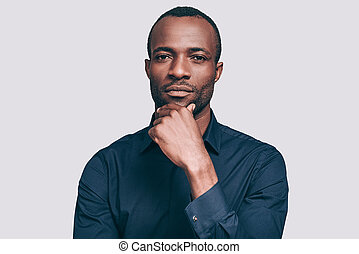 Thinking about solution. Handsome young African man holding hand on chin and looking at camera while standing against grey background