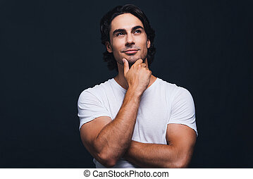 Thinking about solution. Portrait of handsome young man holding hand on chin and looking away with toothless smile while standing against grey background