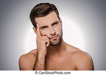 Thinking about solution. Portrait of thoughtful young shirtless man looking at camera while standing against grey background
