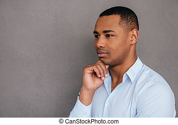 Thinking about solution. Thoughtful young African man holding hand on chin and looking away while standing against grey background
