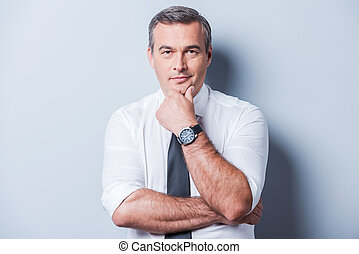 Thinking about your problems. Thoughtful mature man in shirt and tie holding hand on chin and looking at camera while standing against grey background
