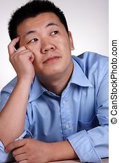 Thinking - An asian guy thinking of something.