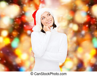 thinking and smiling woman in santa helper hat - christmas,...