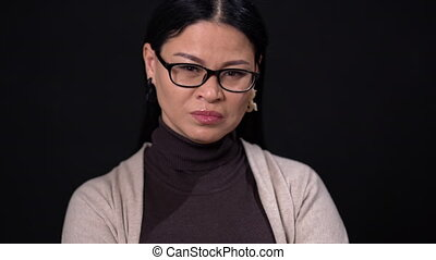 Thinking asian businesswoman in glasses on dark background -...