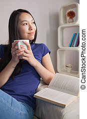 Thinking asian woman sitting on the couch holding mug of coffee