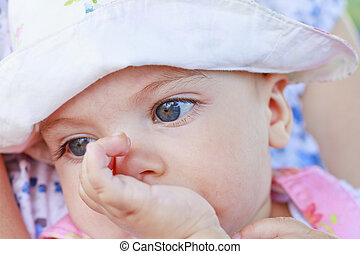 Thinking baby girl with her finger in mouth