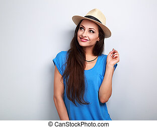 Thinking beautiful woman in hat and blue top looking up on blue background