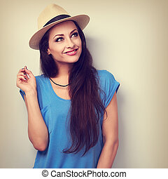 Thinking beautiful woman in hat and blue top looking up. Toned closeup portrait