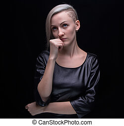 Thinking blond woman in leather dress