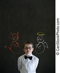 Thinking boy dressed up as business man with chalk angel and devil on shoulder making decision on blackboard background